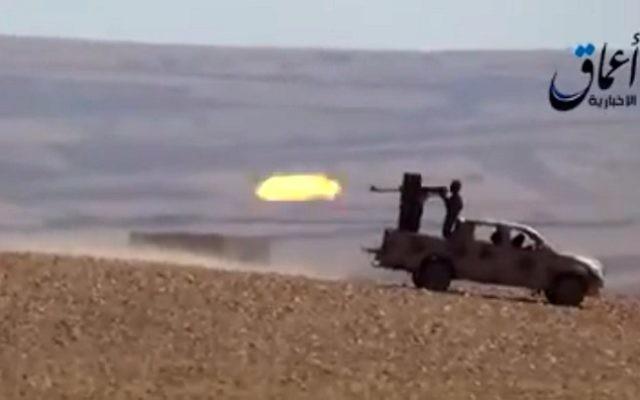 Des combattants du groupe Etat islamique tirant à partir d'un véhicule blindé sur une route menant à Ain al-Arab (Kobané), à la frontière entre la Syrie et la Turquie, capture d'écran YouTube (Crédit : AFP / HO / AAMAQ AGENCE DE NOUVELLES)