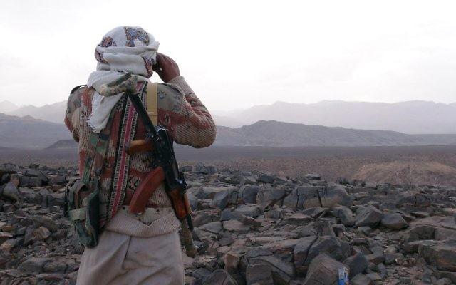 Un membre de la tribu yéménite armée du Comité de la Résistance Populaire soutenant les forces fidèles au président fugitif Abedrabbo Mansour Hadi qui regarde à travers des jumelles dans la région de Jaadan, à Marib, la province est de la capitale, Sanaa, le 9 mai 2015 (Crédit : AFP / STR)