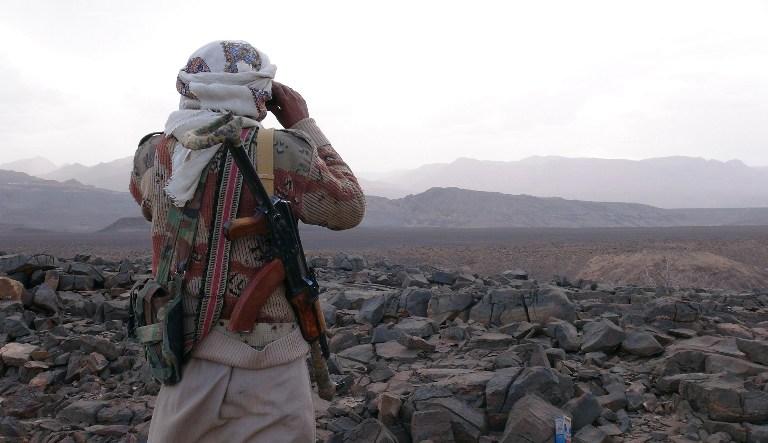 Un membre de la tribu yéménite armée du Comité de la Résistance Populaire soutenant les forces fidèles au président fugitif Abedrabbo Mansour Hadi qui regarde à travers des jumelles dans la région de Jaadan, à Marib, laprovince est de la capitale, Sanaa, le 9 mai 2015 (Crédit : AFP / STR)