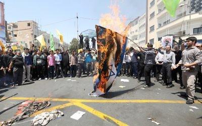 Des manifestants iraniens brûlent un drapeau israélien lors d'une manifestation pour marquer la journée internationale de Al Qods (Jérusalem) à Téhéran le 10 juillet 2015. (Crédit : AFP / ATTA KENARE)