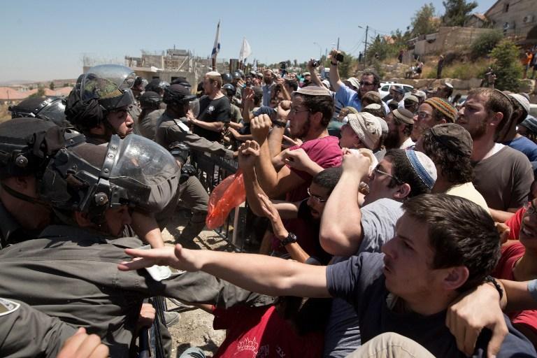 Des résidents d'implantations israéliens aux prises avec les forces de sécurité pour protester contre la démolition des bâtiments Dreinoff dans l'implantation de Beit El, en Cisjordanie, le 29 juillet, 2015. (Crédit : AFP PHOTO / MENAHEM KAHANA)