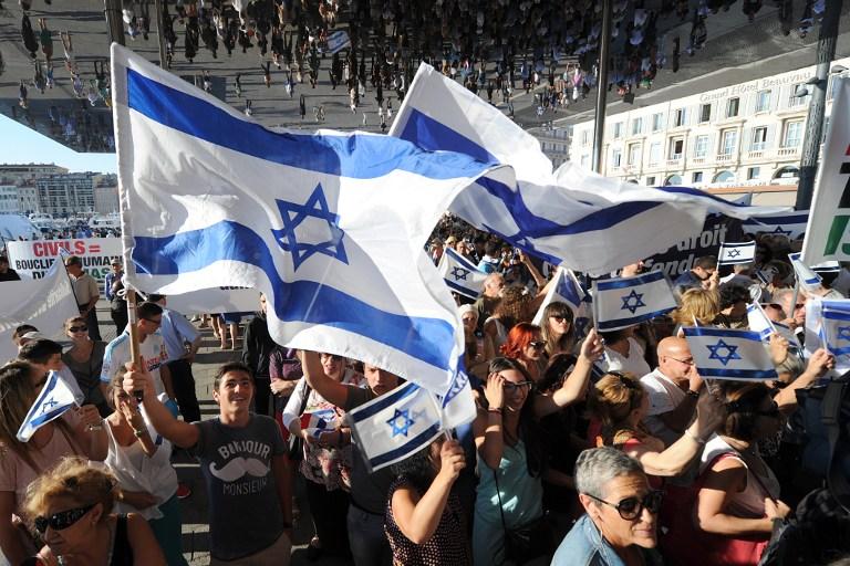 Les gens agitant des drapeaux israéliens lors d'une manifestation de soutien à Israël, le 27 juillet 2014, à Marseille, dans le sud de France (Crédit : AFP PHOTO / Boris Horvat)