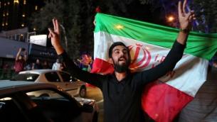 Un Iranien fait le signe de la victoire tandis qu'un autre tient le drapeau national iranien lors des célébrations de la signature de l'accord nucléaire dans le nord de Téhéran le 14 juillet 2015 (Crédit photo: ATTA KENARE/ AFP)