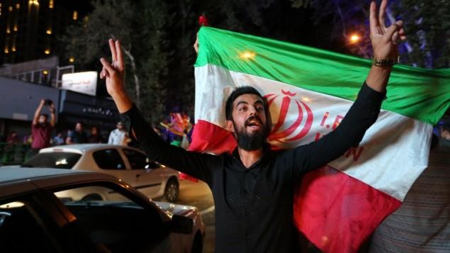 Un Iranien fait le signe de la victoire tandis qu'un autre tient le drapeau national iranien lors des célébrations de la signature de l'accord nucléaire dans le nord de Téhéran, le 14 juillet 2015 (Crédit : ATTA KENARE/ AFP)