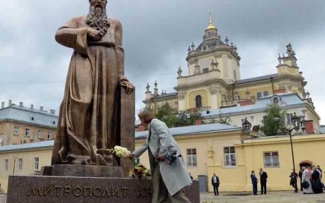Une femme dépose des fleurs devant le monument pour l'Archevêque métropolitain de l'Eglise catholique grecque ukrainienne, Andriy Sheptytsky (1865-1944) après son inauguration pour le 150e anniversaire de sa naissance le 29 juillet 2015 dans le ville ukrainienne de Lviv (Crédit : AFP PHOTO / YURIY DYACHYSHYN)