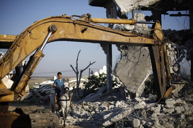 Un Palestinien chevauche son cheval à travers les décombres de bâtiments qui auraient été détruits pendant la guerre de 50 jours entre Israël et le Hamas à l'été 2014, dans la ville de Gaza, le 21 juillet, 2015 (Photo: Mohammed Abed / AFP )