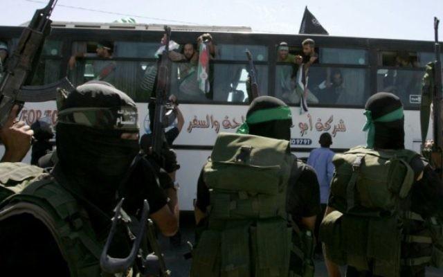 Des membres du Hamas surveillent la rue alors qu'un bus transportant des prisonniers palestiniens arrive dans le passage de Rafah limitrophe avec l'Egypte dans le sud de la bande de Gaza, suite à l'échange Shalit, le 18 octobre 2011 (Crédit : Abed Rahim Khatib / flash 90)