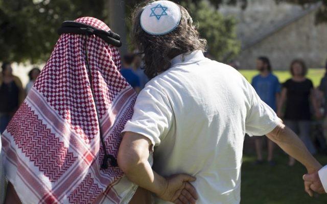 """Haj Ibrahim Ahmad Abu el-Hawa, chef de clan arabe de la région de Jérusalem,  avec un homme juif  devant les murs de la Vieille Ville de Jérusalem, pendant """"The Big Hug"""", le 24 juin  2013. (Crédit : Sarah Schuman/Flash90)"""