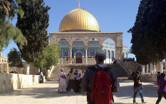 Un visiteur juif au mont du Temple regardant le Dôme du Rocher en 2013 (Crédit : Sliman Khader / Flash90, File)
