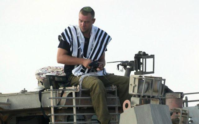 Un soldat de Tsahal prie au sommet d'un bulldozer blindé de Tsahal près de la frontière de Gaza dans le sud d'Israël, le premier jour de l'opération Bordure protectrice le 8 juillet 2014 (Crédit : David Buimovitch / Flash90)