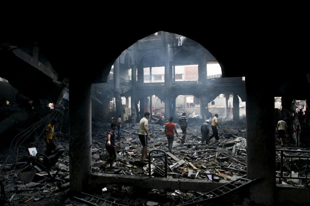 Des Palestiniens inspectent les décombres d'un centre commercial détruit après un raid aérien israélien dans la ville de Rafah, dans le sud de la bande de Gaza, le 24 août 2014 (Crédit : Abed Rahim Khatib / Flash90)