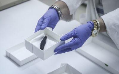 Un morceau d'un rouleau de la Torah incendié montré par le personnel dans un laboratoire de l'Autorité des Antiquités d'Israël le 20 Juillet, 2015. (Crédit : Flash90)