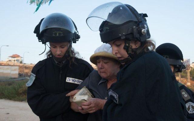 Les forces de sécurité israéliennes emmènent une résidente d'implantation venue pour manifester contre la démolition de deux immeubles d'habitation dans l'implantation juive de Beit El, le 28 juillet 2015 (Crédit : Nati Shohat / FLASH90)