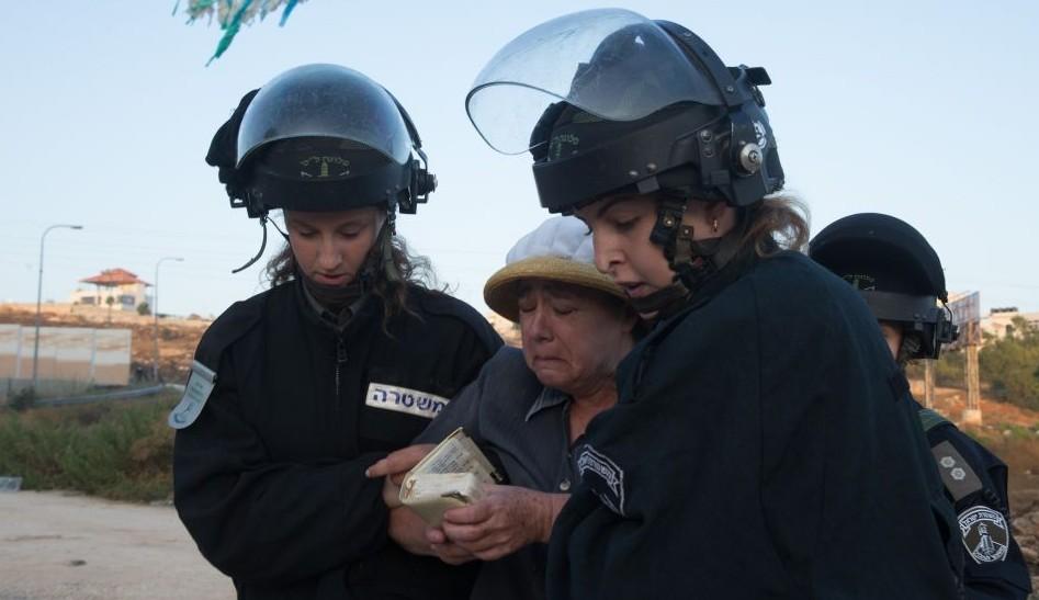 Les forces de sécurité israéliennes emmène une résidente d'implantation venue pour manifester contre la démolition de deux immeubles d'habitation dans l'implantation juive de Beit El, le 28 juillet 2015 (Crédit : Nati Shohat / FLASH90)