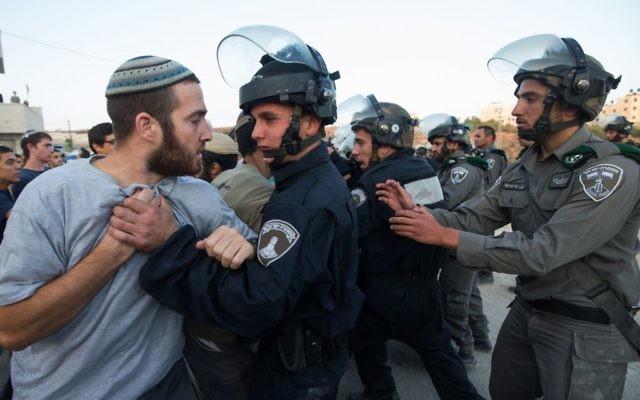 Les forces de sécurité israéliennes affrontant les résidents des implantations qui se sont barricadés pour tenter d'empêcher la démolition des bâtiments construits illégalement dans l'implantation juive de Beit El  le 28 juillet 2015 (Crédit : Nati Shohat / FLASH90)