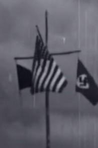 Trois drapeaux déployés dans un camp de jeunesse nazi aux États-Unis en 1937: l'emblème du camp, le drapeau américain, et la croix gammée (Crédit : Capture d'écran YouTube)