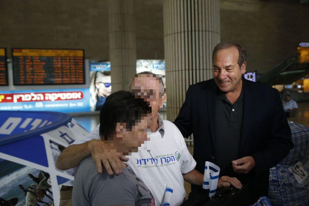 Rabbi Yechiel Eckstein, le président de l'IFCJ,  accueille des immigrants ukrainiens David et son épouse à leur arrivée à l'aéroport Ben Gurion, le mercredi 1er Juillet 2015 (Crédit : Baz Ratner)
