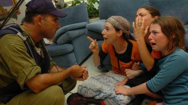 Un soldat israélien évacue trois femmes de leur maison de l'implantation juive de Neve Dekalim, dans la bande de Gaza, en 2005. (Crédit : Flash90)