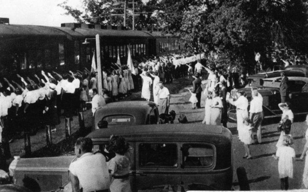 """Le train """"Camp Siegfried spécial"""" arrivant à Yaphank, à Long Island, accueillis par des saluts hitlériens par ceux qui attendent sur le quai de la gare (Crédit : Historical Society de la ville de Brookhaven )"""