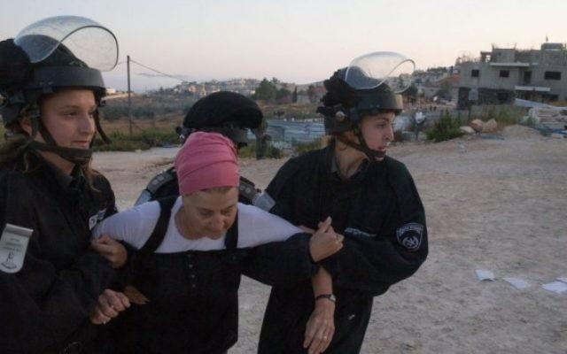 Les forces de sécurité israéliennes traînent une habitante juive venue manifester contre une évacuation dans l'implantation de Beit El, le 28 Juillet 2015 (Crédit photo: Nati Shohat / Flash90)