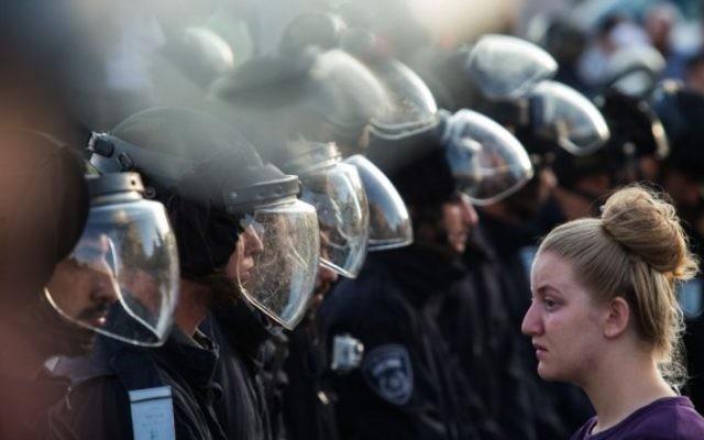 Les forces de sécurité israéliennes face à un manifestante juive lors d'une évacuation dans l'implantation de Beit El, le 28 Juillet 2015 (Crédit photo: Nati Shohat / Flash90)
