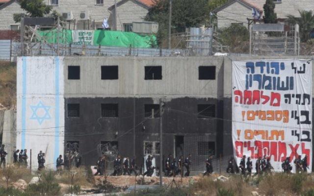 Les forces de sécurité israéliennes encerclent un bâtiment dans lequel des activistes se sont barricadés pour résister à son évacuation dans l'implantation de Beit El en Cisjordanie le 28 juillet 2015 (Crédit photo: Flash90)