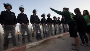 Les forces de sécurité israéliennes affrontent les résidents de l'implantation de Beit El  barricadés dans une tentative d'empêcher la démolition des bâtiments construits illégalement,  le 28 juillet 2015 (Crédit photo: Nati Shohat / Flash90)