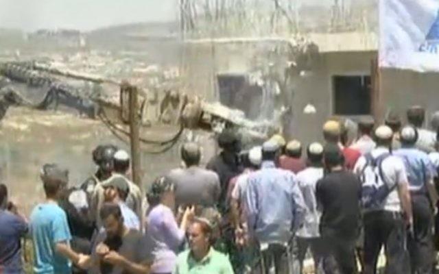 Un engin démolissant un immeuble dans l'implantation de Beit-El le 29 juillet 2015 (Capture d'écran Ynet)