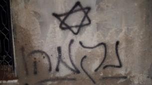 Une étoile de David et  le mot 'Revanche' en hébreu sont peints à la bombe sur les murs d'une maison palestinienne qui a été incendiée  dans le village palestinien de Duma, près de Naplouse, le 31 juillet 2015 (Crédit : Zacharia Sadeh / Rabbis for Human Rights)