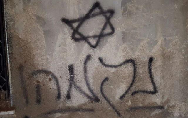 """Une étoile de David et  le mot """"Revanche"""" en hébreu sont peints à la bombe sur les murs d'une maison palestinienne qui a été incendiée  dans le village palestinien de Duma, près de Naplouse, le 31 juillet 2015 (Crédit : Zacharia Sadeh / Rabbis for Human Rights)"""