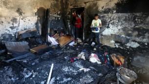 Des palestiniens examinent les dégâts d''une maison incendiée où un bébé a été tué, apparemment par des terroristes juifs, dans le village de Duma en Cisjordanie, le 31 juillet 2015. (Crédit : AFP/Jaafar Ashtiyeh)