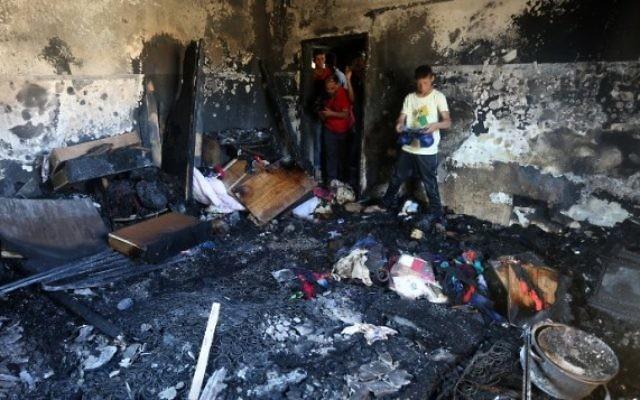 Des palestiniens examinent les dégâts d''une maison incendiée où un bébé a été tué, apparemment par des terroristes juifs, dans le village de Duma en Cisjordanie le 31 juillet, 2015  (Jaafar Ashtiyeh / AFP)