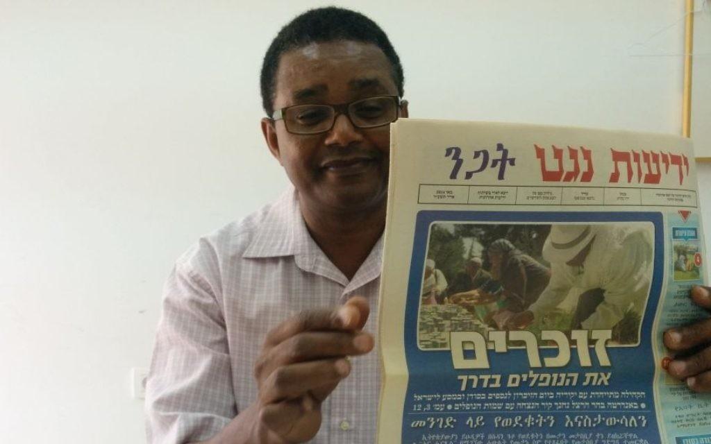Dr Anbessa Teferra, professeur de langues sémitiques à l'université de Tel-Aviv, tient un numéro de Yedioth Negat, journal en amharique. (Ilan Ben Zion / Times of Israel)