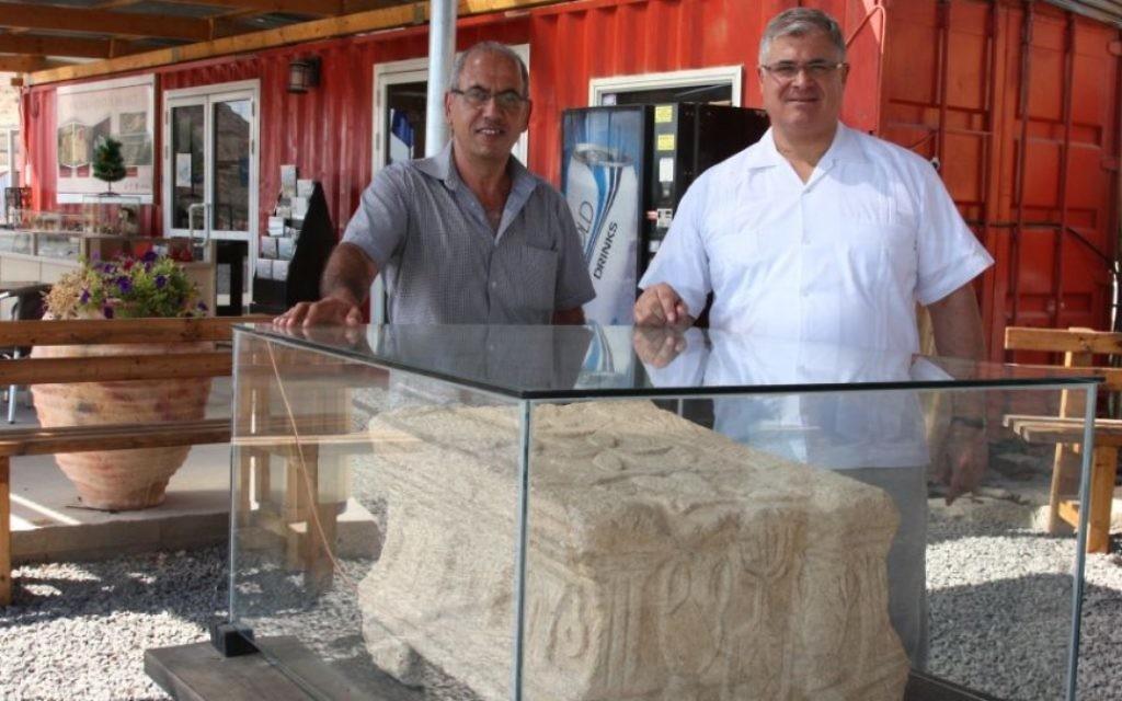 Père Juan (à droite) et l'archéologue Arfan Najjar avec la pierre de l'autel à Magdala (Crédit : Shmuel Bar-Am)