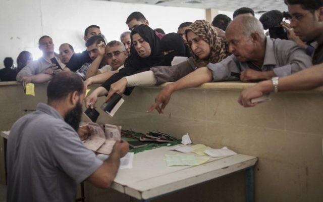 Des Palestiniens se rassemblent à la frontière de Rafah, dans le sud de la bande de Gaza, où ils attendent l'autorisation d'entrer en Egypte, le 12 juin 2015. (Crédit : AAED Tayeh/Flash90)