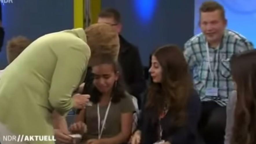 La chancelière allemande Angela Merkel tente de réconforter Reem Sawhil, une jeune réfugiée palestinienne menacée d'expulsion, au cours d'un débat télévisé sur les politiques d'asile du pays (Crédit : Capture d'écran)