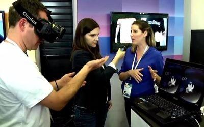 Un utilisateur (à gauche) montre comment le casque Oculus VR fonctionne tandis que Laura Rosbrow de Geektime (centre) interview une représentant de Pebbles, Renana Perlovitch (Crédit : Geektime)