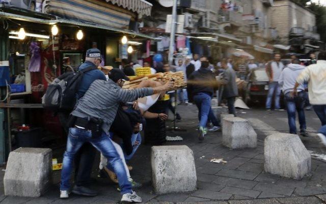 Un policier en civil utilise un spray lacrymogène pour disperser les manifestants dans la Vieille Ville de Jérusalem le 24 septembre 2013 (Crédit : Sliman Khader / Flash90)