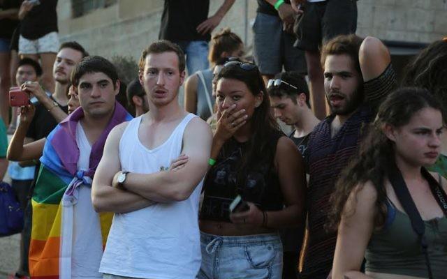 Des participants à la marche de la gay pride à Jérusalem, le 30 juillet 2015, devant des participants qui ont été poignardés (Crédit : Eric Cortellessa/Times of Israel)
