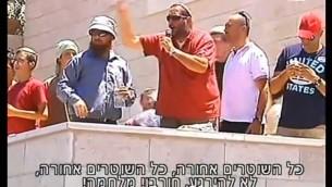 Un homme harangue la foule des manifestants à Beit El, le 29 juillet 2015 (Crédit : Capture d'écran Deuxième chaîne)