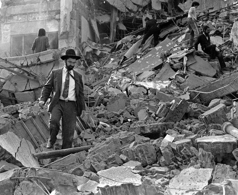Un homme marche dans les décombres après l'explosion d'une bombe à l'Association mutuelle israélite argentine (centre AMIA) à Buenos Aires, le 18 juillet 1994, tuant 85 personnes et en blessant environ 300 autres. (Crédit : Ali Burafi/AFP)