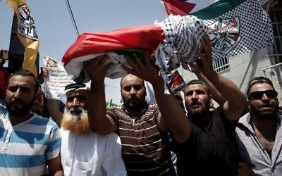 Les membre de la famille portant le corps du bébé palestinien, Ali Saad Dawabsha, décédé après que sa maison a été incendiée par des résidents juifs, lors de ses funérailles dans le village cisjordanien de Douma le 31 juillet 2015 (Crédit : AFP PHOTO / THOMAS COEX)