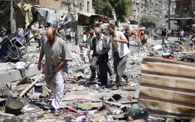 Des Syriens marchent au milieu des décombres de frappes aériennes des forces gouvernementales syriennes sur un marché, à Douma, zone contrôlée par les rebelles, à l'est de Damas, le 16 août 2015. (Sammer al Doumy / AFP)