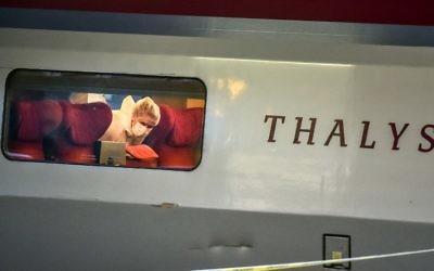 Un agent de police examine la scène du crime à l'intérieur d'un train Thalys la SNCF à la gare d'Arras, Nord de la France, le 21 août, 2015. Un homme armé a ouvert le feu dans un train blessant 3 personnes avant d'être maîtrisé par les passagers (Crédit : AFP PHOTO / PHILIPPE HUGUEN)