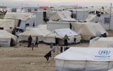 Photo prise le 11 janvier 2015, montrant des réfugiés syriens debout à côté de tentes de l'ONU au camp de réfugiés de Zaatari, au nord est de la capitale jordanienne Amman. Plus d'1,1 millions de Syriens ont  passé la frontière vers le Liban et environ 600 000 sont en Jordanie, selon le HCR, le 28 Août 2015. Amman avance le chiffre de 1,4 million, soit 20 % de la population du royaume qui est pauvre en ressource (Cédit : AFP PHOTO / KHALIL MAZRAAWI)