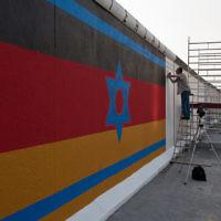 La fresque murale du mur de Berlin, peint à l'origine en 1988 par Günther Schaefer pour le 40e anniversaire de la Nuit de cristal en Allemagne nazie. La fresque est composée d'un drapeau israélien superposé sur un drapeau allemand (Crédit : CC-BY-SA Maartmeester, Flickr)