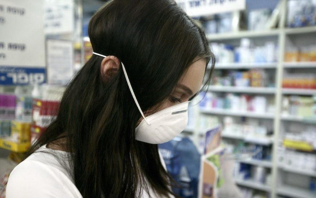 Une employée dans une pharmacie à Jérusalem (Crédit : Abir Sultan/Flash90)