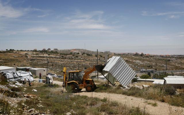 Photo des forces de sécurité israéliennes en train de démolir une structure construite illégalement dans un avant-poste en Cisjordanie (Crédit : Miriam Alster / flash 90)