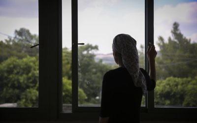 Une jeune femme religieuse regarde par la fenêtre (Hadas Parush/Flash90)