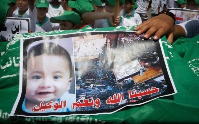 Des enfants palestiniens portent un brancard funèbre avec une image du petit Ali Saad Dawabsha, l'enfant qui a été brûlé à mort par des extrémistes juifs, le 1er août, 2015, lors d'une manifestation à Khan Yunis, dans la bande de Gaza, simulant un enterrement organisée par les partisans palestiniens du Hamas en réaction à la mort du bébé (Crédit : Abed Rahim Khatib / flash 90)